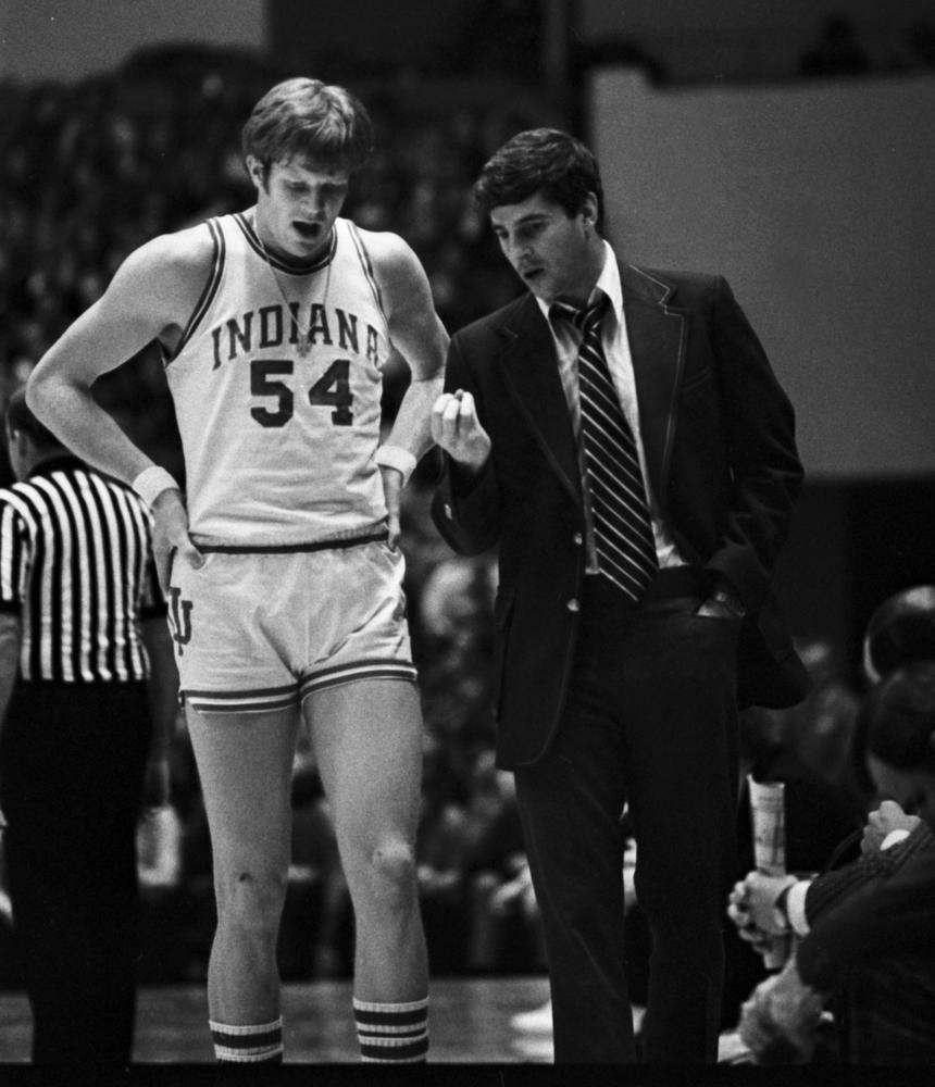 Head coach Bob Knight talks with freshman big man Kent Benson. Benson is seen sporting the original pitchfork style shorts, introduced during the 1972-73 season.